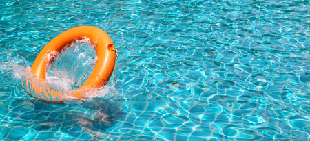 Orange life buoy is thrown to clear water swimming pool, for the emergency case