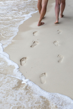 The sweet couple holding hands walking on the beach and their footprints in the sand around seashore.