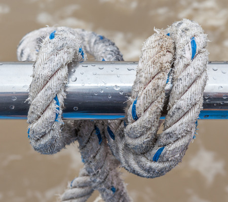 cleat: Old white and blue knot rope tied around steel holder on boat or yacht