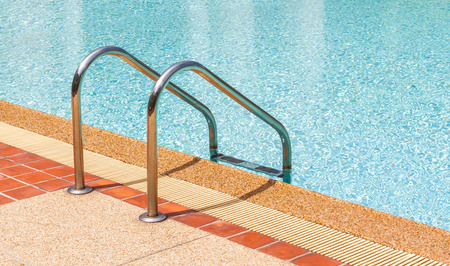 Ladder and clear swimming pool in summer time photo