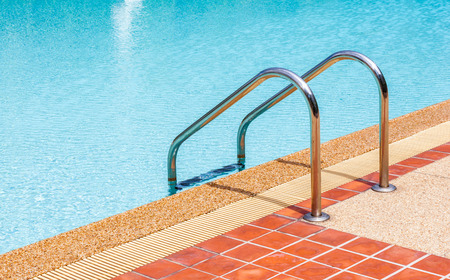 The steel ladder of swimming pool in summer time photo