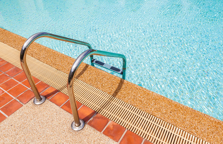 The ladder and blue clear swimming pool in summer time photo