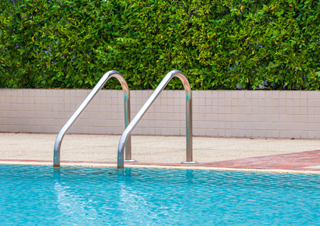 Grab bars ladder in the blue swimming pool, in summer time photo