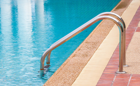 Steel ladder in a blue swimming pool photo