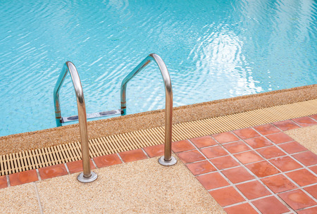 Ladder of swimming pool in summer time photo