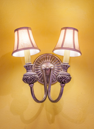 yellow lamp: The vintage wall lamp hanging on the yellow wall