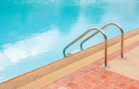 Grab bars ladder in the blue swimming pool, summer time photo