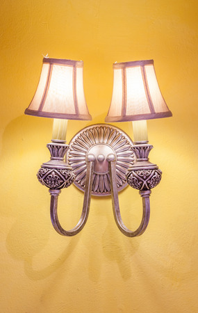 sconce: The vintage wall lamp hanging on the yellow wall