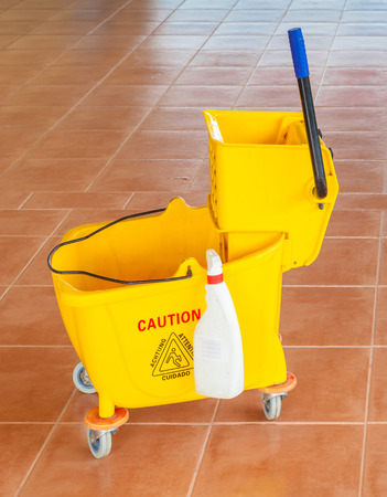 Yellow mop bucket and wringer with caution sign on the floor in office building, for cleaning photo