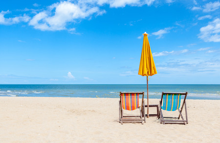 Pair of colorful beach chair with sun umbrella on beautiful beach. Concept for rest, relaxation and holiday.