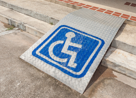 wheelchair access: Ramped access, using wheelchair ramp with information sign on floor background for disabled people.