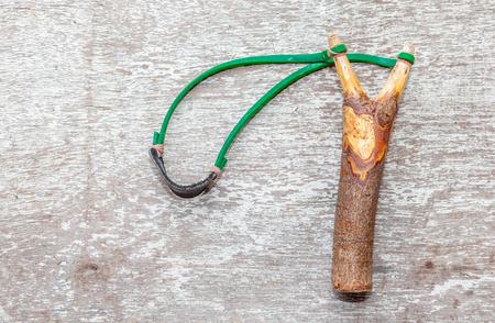 The old slingshot on old wood background photo