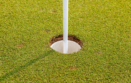 Close up of golf hole and flag on green grass of golf course photo