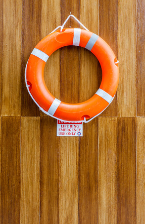 The orange life buoy hanging on the wood wall around the swimming pool photo