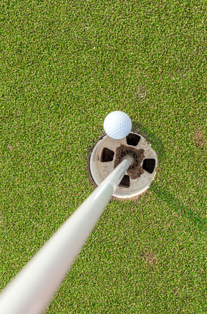 Aerial view of golf ball near pin and hole on green grass of golf course photo