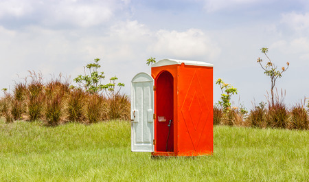 water closet: Standalone of red water closet or toilet in the green meadow with clear blue sky.