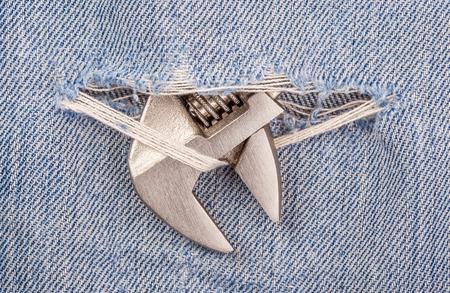 pierce: Head of pliers black handle tool pierce through old blue jeans background