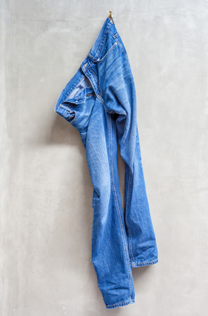 jeans woman: blue jeans is hanging on the exposed concrete wall in bathroom. Stock Photo