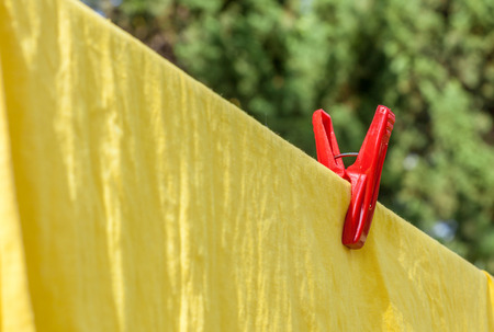 The red plastic clothespin is contrasting on the clothesline with yellow cotton cloth photo