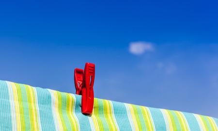 The red plastic clothespin is on the clothesline and colored cotton with blue sky background. photo