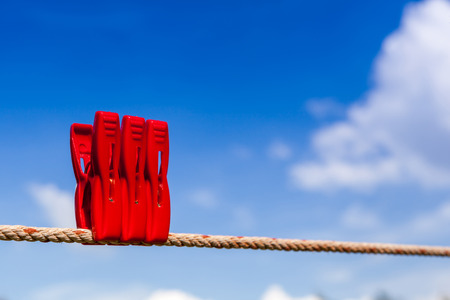 Three red plastic clothespins hang on a laundry line outside with the bright blue sky. photo