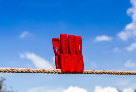 Three red plastic clothespins hang on a laundry line with the blurry blue sky background. photo