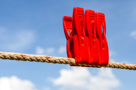 Three red plastic clothespins and a laundry line outside with the blurry blue sky background. photo