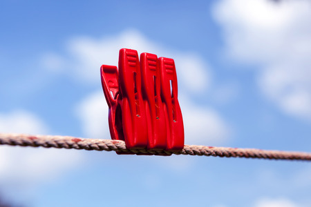 Three red plastic clothespins are on clothesline against blurry blue sky background. photo
