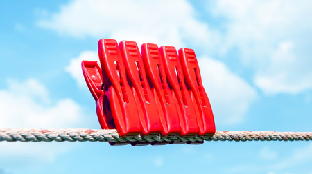 Five red plastic clothespins hang on the clothesline with blurry blue sky background. photo