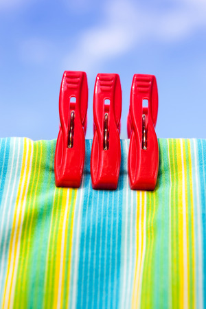 Three red plastic clothespins and multicolor cotton on clothesline with the blurry blue sky background. photo