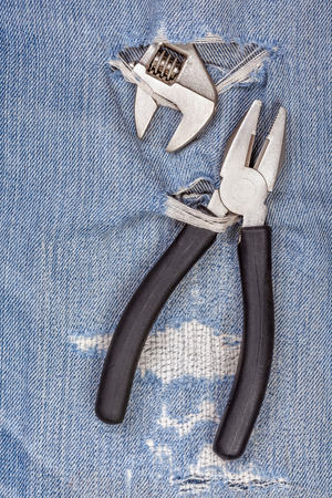 durchstechen: 2 Arten von Zangen schwarzen Griff Werkzeug durchstechen alten Jeans Hintergrund, Konzept f�r die Befestigung und n�tzliche Wartung.