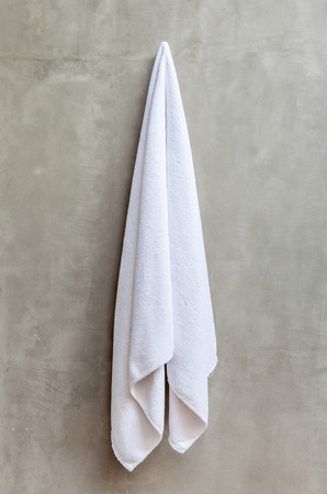 Clean and white towel is hanging on a hanger with concrete wall in the bathroom
