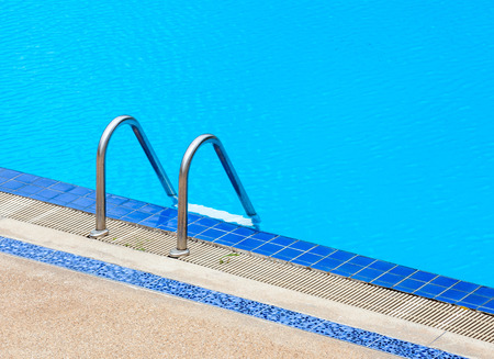 A view of a light clear blue swimming pool with steel ladder, outdoor swimming pool. photo