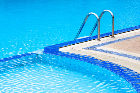 A view of curved light clear blue swimming pool with steel ladder, outdoor swimming pool. photo