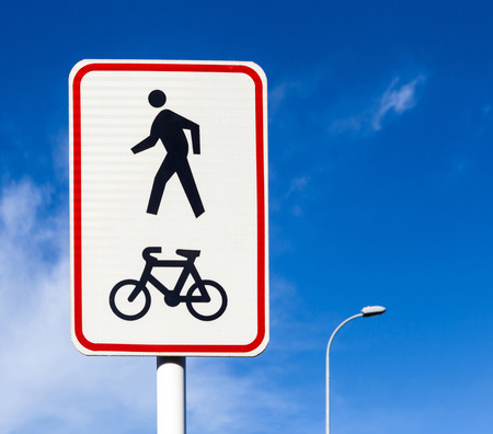 walking pole: Bicycle and pedestrian lane road sign on pole post, bike cycling and walking walkway footpath route traffic roadside signal. Stock Photo