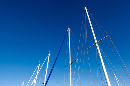 Looking up the mainmasts and blue sky background, around port. photo