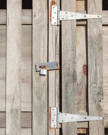 locked door: Old rustic padlock on wooden door in countryside, concept of security.
