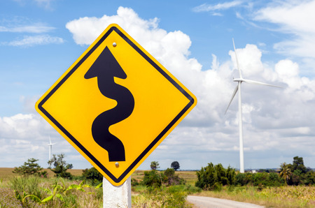 Winding road sign with windmill background in wind farm, Korat province in Thailand. photo