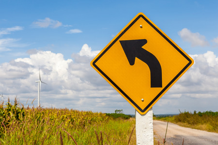 Left curved warning sign with windmill background in wind farm, Korat province in Thailand photo