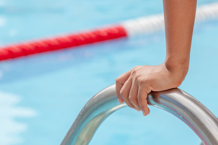 Start swimming race concept with closeup the hand grab on ladder bar of swimming pool. photo
