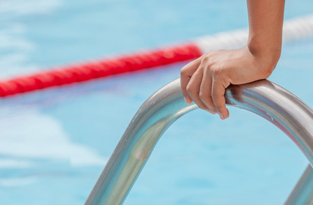 Closeup the hand grabs on the metallic bar of swimming pool, ready entrance to swimming pool competitions. photo