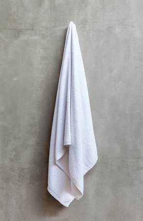 exposed concrete: White and clean towel is hanging on the exposed concrete wall in the bathroom. Stock Photo