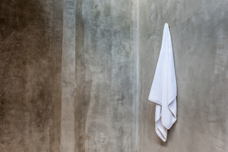 exposed concrete: Hanging white and clean towel draped on exposed concrete wall in the bathroom.