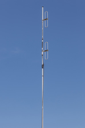 dipole: Looking up the telecommunication dipole antenna with blue sky background.