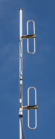 dipole: Close up Cellular transmitter, dipole antenna for telecommunications with clear blue sky background. Stock Photo