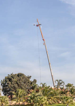 The photo of hoisting crane working for telecommunication site and antenna tower. photo