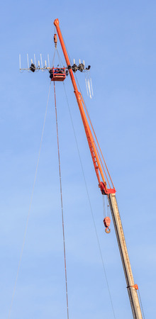 Telecommunication site, hoisting crane tower lifting the dipole antenna and blue sky background. Stock Photo