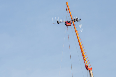 dipole: The construction site of telecommunication tower with lifting crane is working in blue sky sunny day.