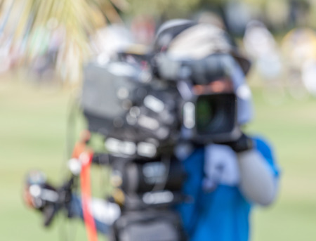 unclear: Blurred background of sport photographer is working during golf tournament in golf course for live broadcasting.