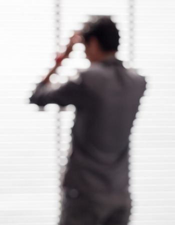 forced: Blurred picture of young businessman in office is forced by under pressure from competitors.